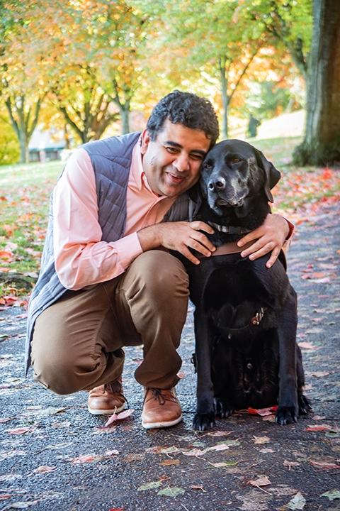 Amit Ahuja crouching next to his black Lab guide dog, Tashi.