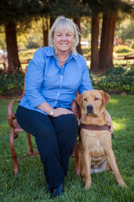 A portrait of Joan Boyd sitting next to a yellow Lab guide dog.