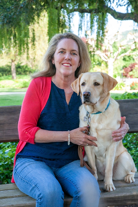 VP of Marketing and Communications Karen Woon, seated on a bench next to a yellow Lab.