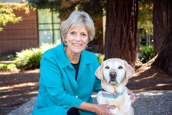 Kathy Riggins kneeling next to a yellow Lab.