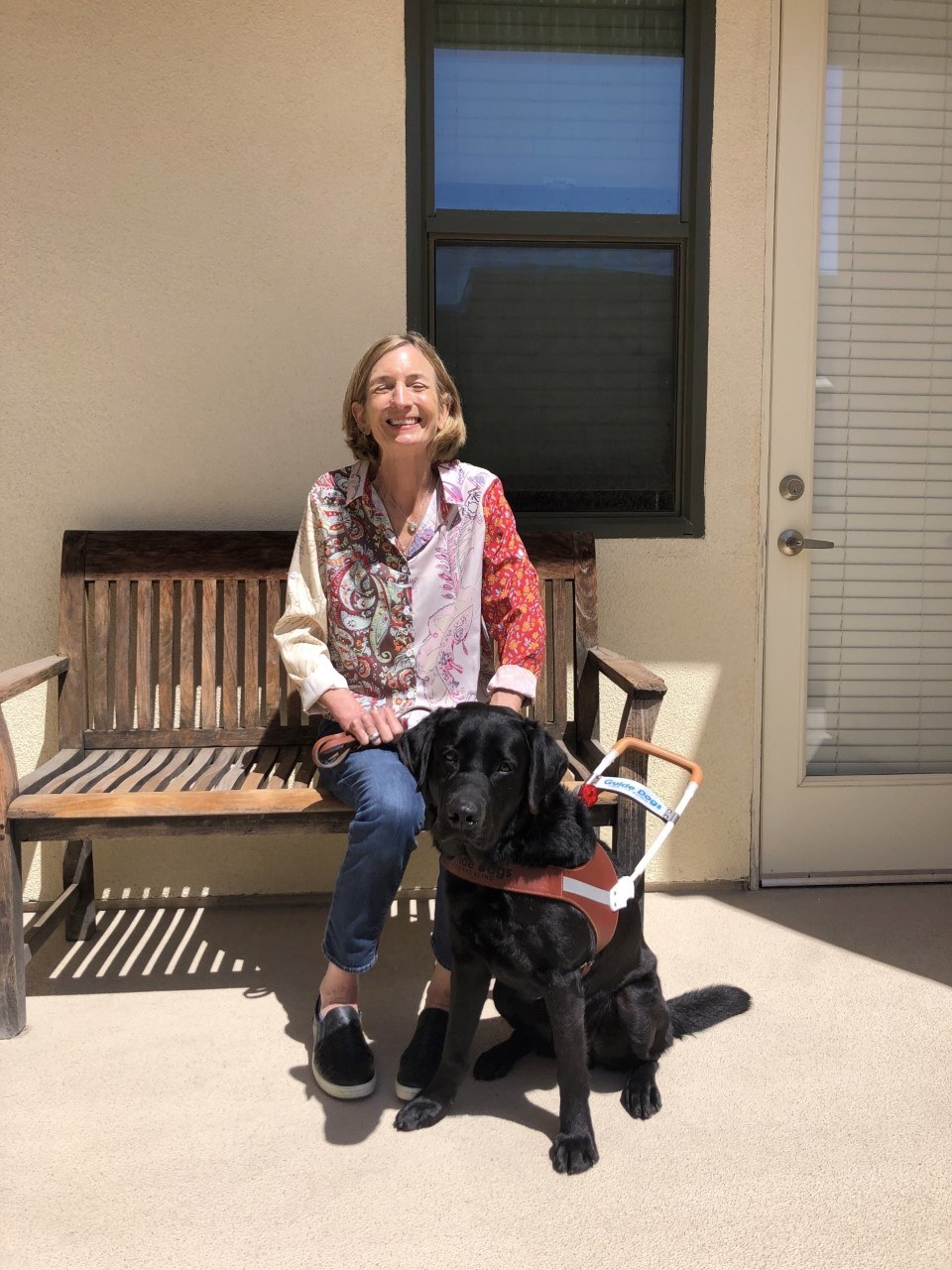 Kelly is seated on a sunny bench beside her black Lab guide dog.