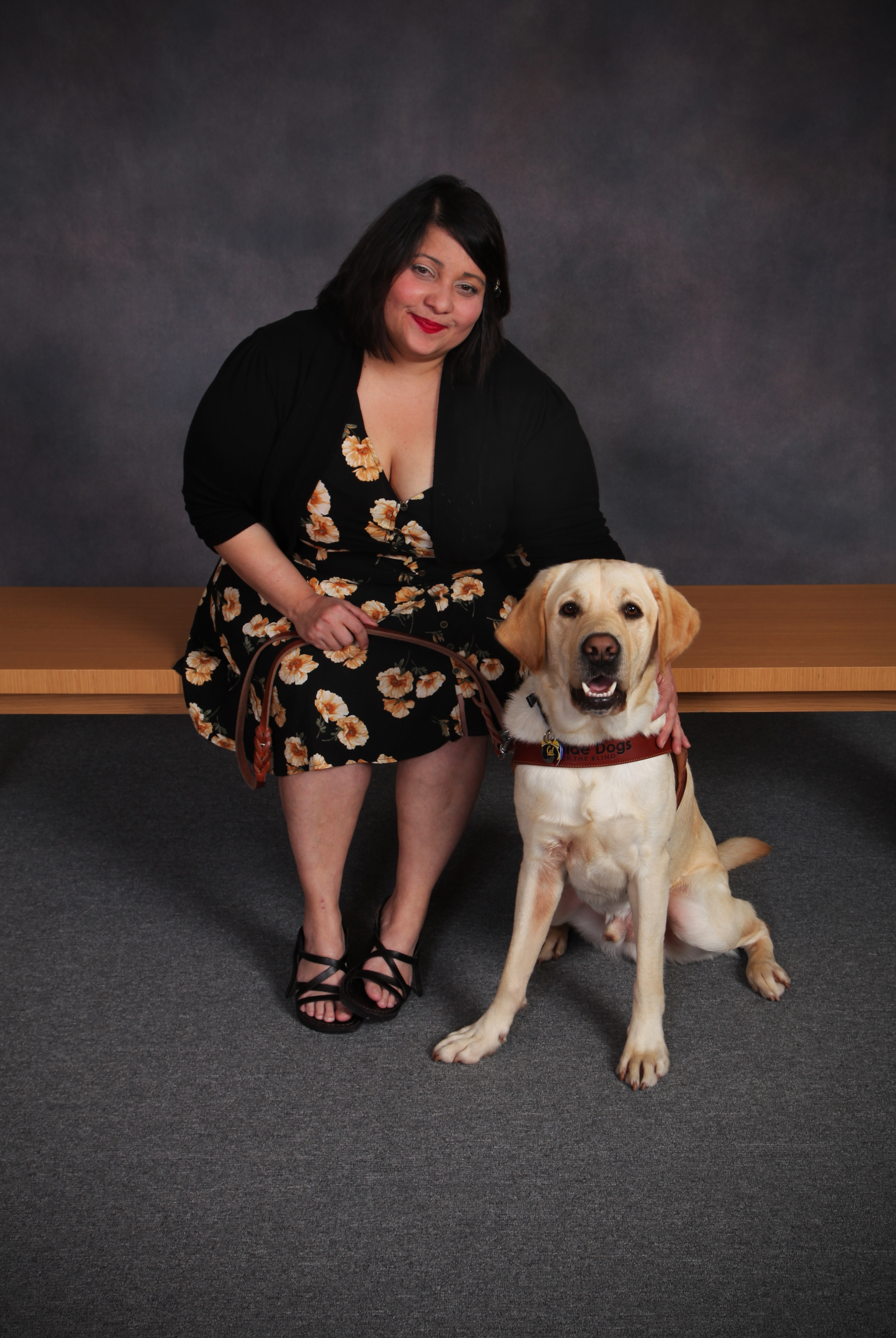 Melba is seated beside yellow Lab guide dog, Chad, in their formal class graduation photo.
