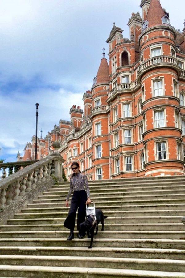 GDB Grad Aria Mia Loberti and black Lab guide dog Ingrid descend the stairs at Royal Holloway University