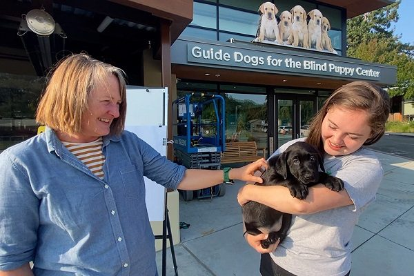 Two volunteer puppy raisers embrace a black Lab puppy in front of the GDB puppy center.