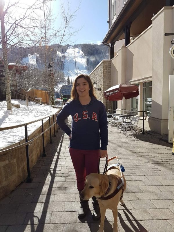 Letticia walks through the Olympic Village in Colorado Springs with her guide dog, Philly.