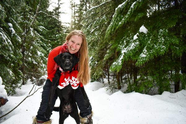 Jamie Mattison with a black Lab on a snowy forested path.