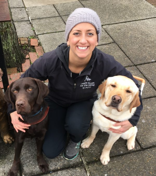 Guide Dog Mobility Instructor Megan Dodder kneeling with two guide dogs, a chocolate Lab and a yellow Lab.