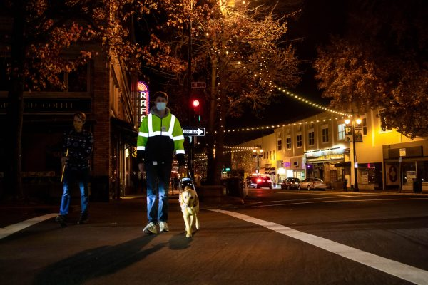 A young man wearing a reflective safety jacket walking with his guide dog across a street at night.