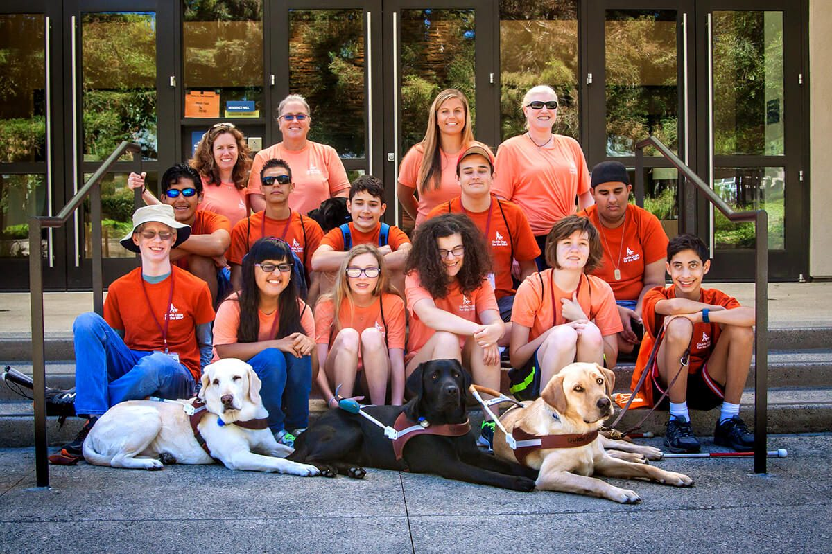 A group shot of camp GDB participants, including three guide dogs.