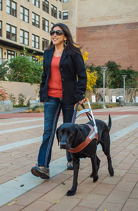 Melissa Hudson walking with her black Lab guide dog, Camry.