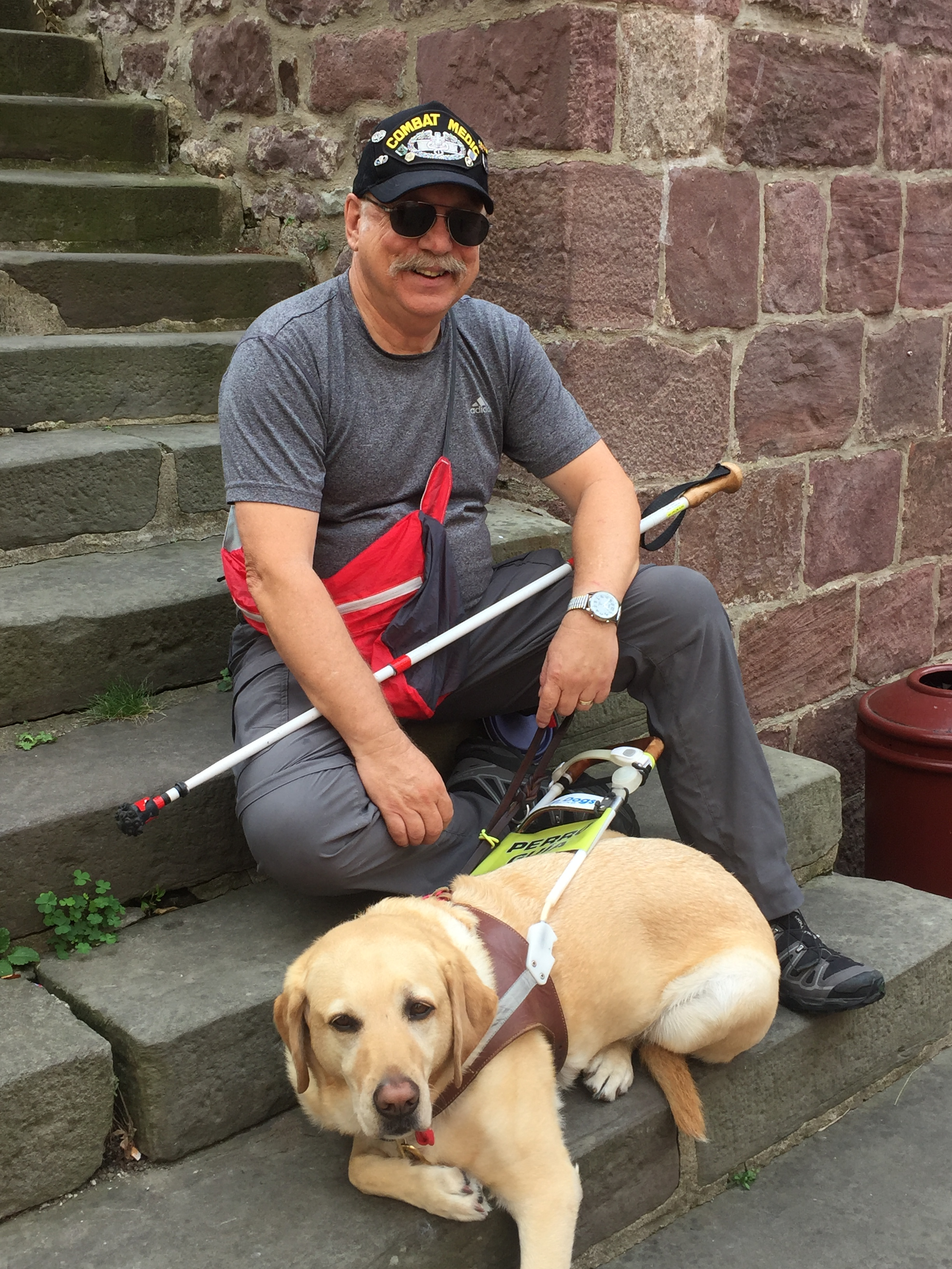 Phil (wearing his Army combat medic hat and sunglasses) sits on concrete steps with guide dog Jeff (yellow Lab)