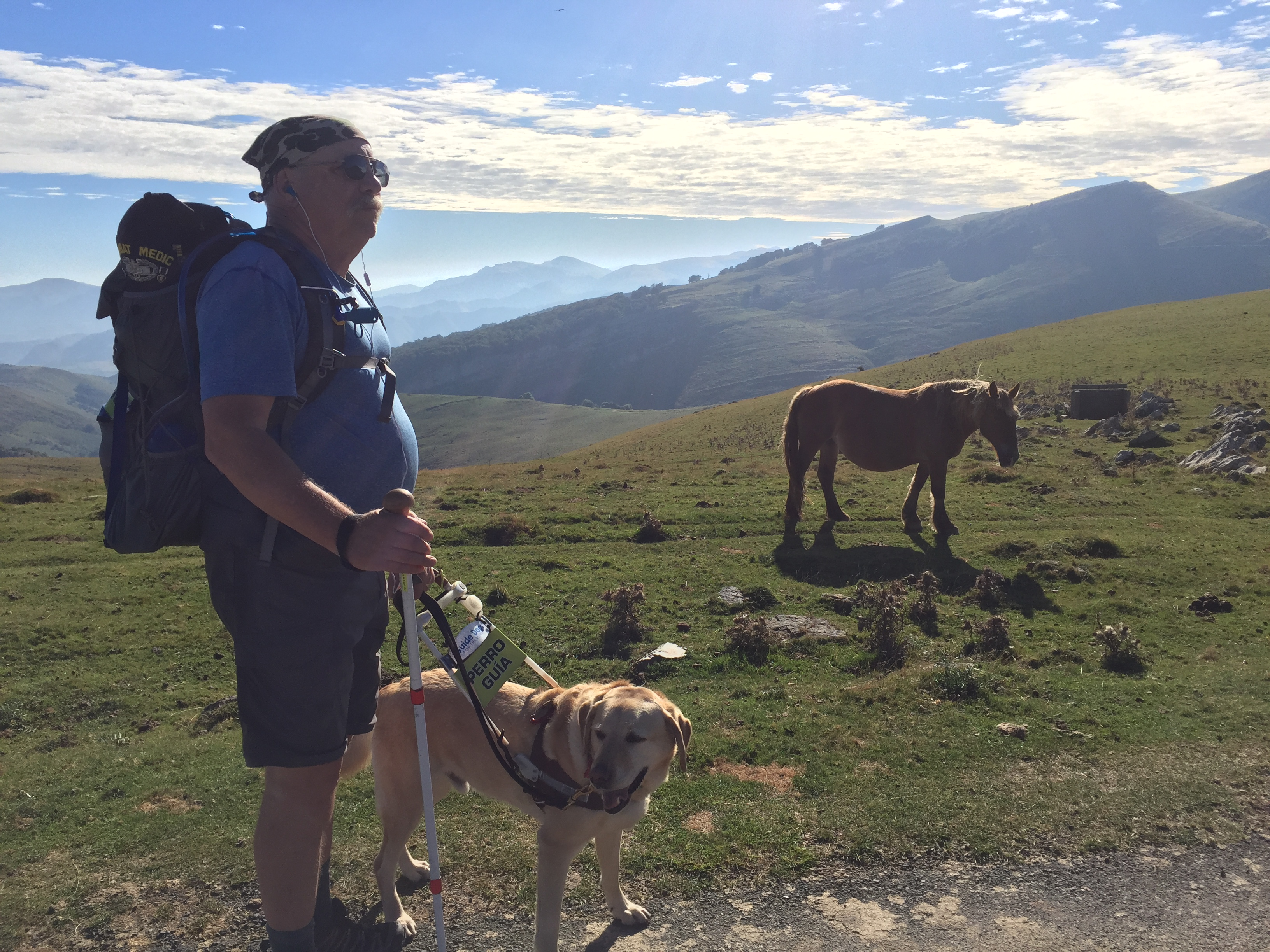 Phil (wearing a backpack and walking pole) stops on the trail with guide dog Jeff (yellow Lab) with a brown horse and mountains in the background.