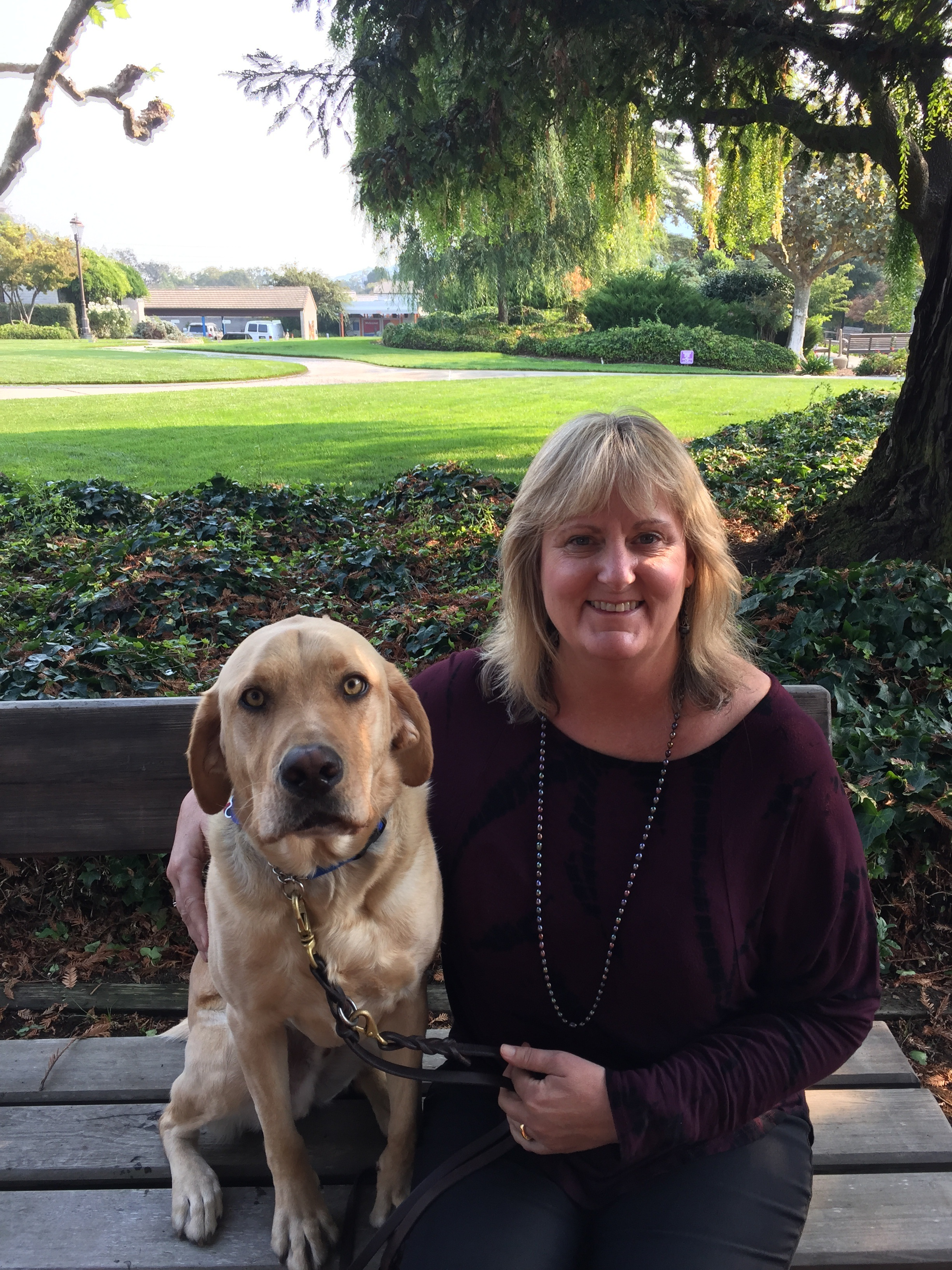 Sheri sits on a bench on GDB's CA campus. She has her arm around a yellow Lab.