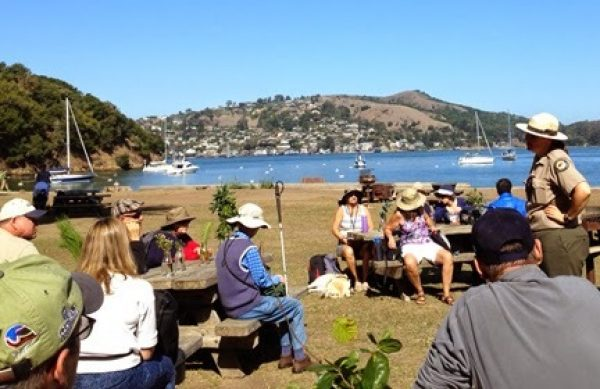 Ranger Casey Dexter Lee greets the Foggy Doggies group on a beautiful sunny day with the bay in the background.