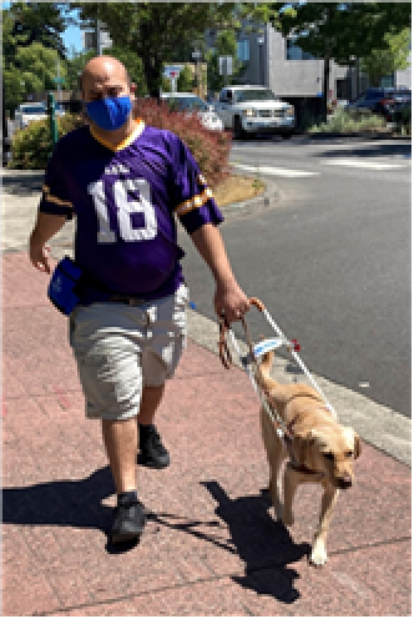 Dimitrios walks down a street with his guide dog Cami
