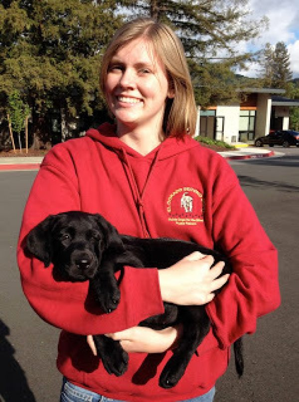 Gina holding a black Lab puppy in her arms.