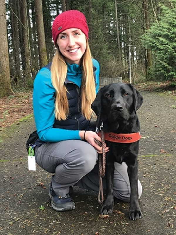 Guide Dog Mobility Instructor Katelyn Almon with a black Lab guide dog.