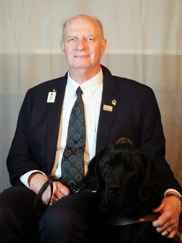 A portrait photograph of a man wearing a suit and sitting next to his guide dog.