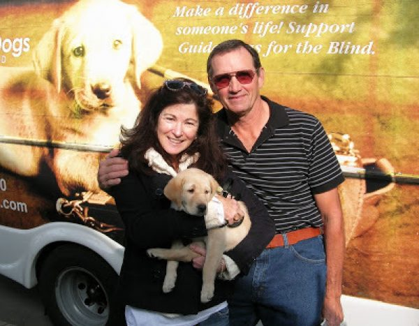 Nancy and Don Bloyer with yellow Lab guide dog puppy January in front of the GDB Puppy Truck.