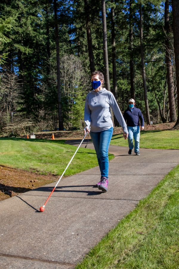 GDB Client Sherry Brackett navigates a wooded trail with a white cane. O&M Manager Marc Gillard follows behind her.