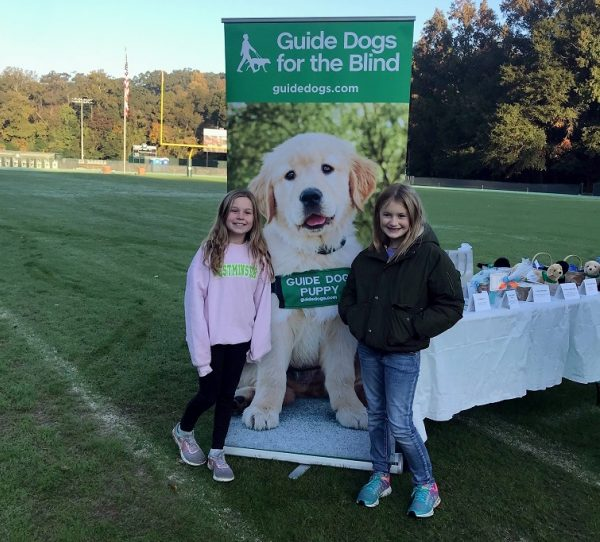 Sloane (left) and a classmate on an athletic field with a GDB banner and a fun run table.