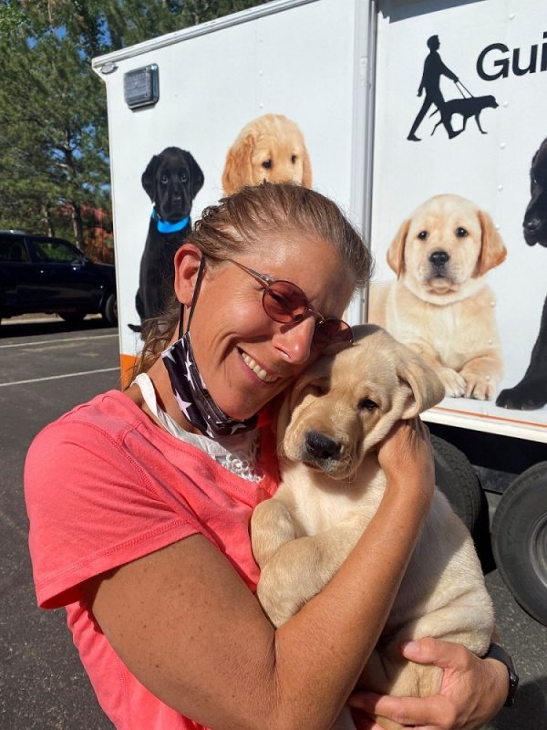 Puppy raiser Wendy Davis smiles as she holds a yellow Lab puppy in front of the puppy truck