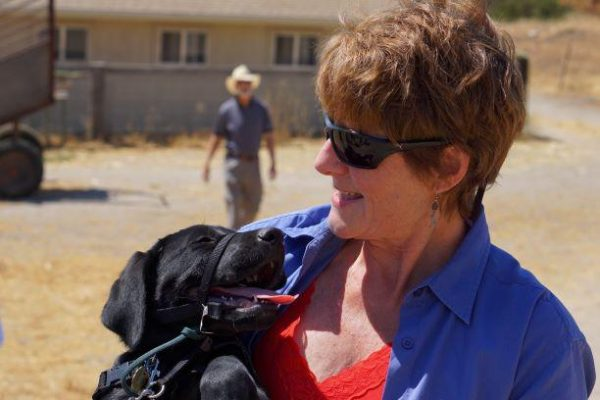 Tami gazes down at a black Lab puppy she holds